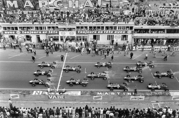 Graham Hill, Lotus 49 Ford, Jack Brabham, Brabham BT24 Repco, and Dan Gurney, Eagle T1G Weslake, lead Jim Clark, Lotus 49 Cosworth, Bruce McLaren, Eagle T1G Weslake, Denny Hulme, Brabham BT24 Repco, Chris Amon, Ferrari 312, Jochen Rindt, Cooper T81B Maserati, Chris Irwin, BRM P83, Jackie Stewart, BRM P261, Jo Siffert, Cooper T81 Maserati, Pedro Rodriguez, Cooper T81 Maserati, and Mike Spence, BRM P83, at the start.