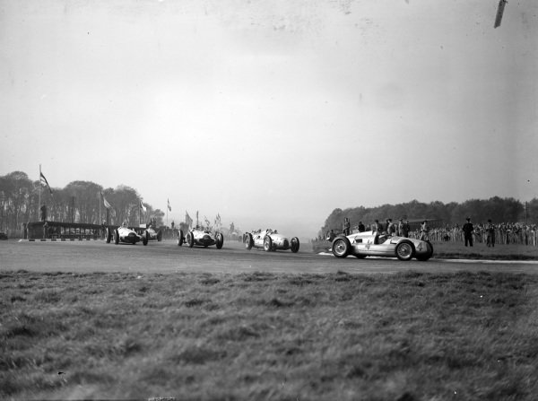 Tazio Nuvolari, Auto Union D, leads Hermann Müller, Auto Union D, and the rest of the field at the start.