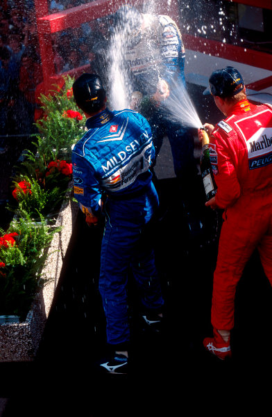1994 Belgian Grand Prix.Spa-Francorchamps, Belgian.26-28 August 1994.Michael Schumacher (Benetton Ford) 1st position, but later disqualified because his skidblock or plank from the car's undertray was found to be below the required legal measurement sprays champagne with Mika Hakkinen (McLaren Peugeot) now 2nd position over Damon Hill (Williams Renault) now 1st position on the podium. Ref-94 BEL 05.World Copyright - LAT Photographic
