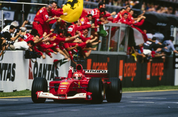Michael Schumacher, Ferrari F2001, celebrates as he crosses the finish line and takes the chequered flag.