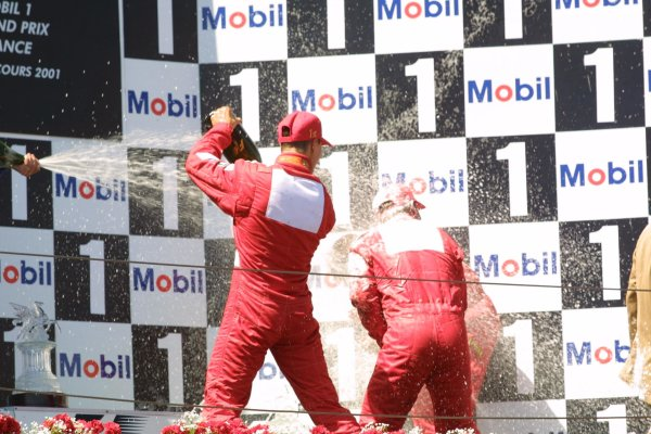 2001 French Grand Prix - RaceMagny-Cours, France. 1st July 2001Race winner Michael Schumacher, Ferrari F2001, and team mate Rubens Barrichello (3rd), Ferrari F2001, spray the champagne. Podium.World Copyright - LAT Photographicref: 8 9 MB Digital File only