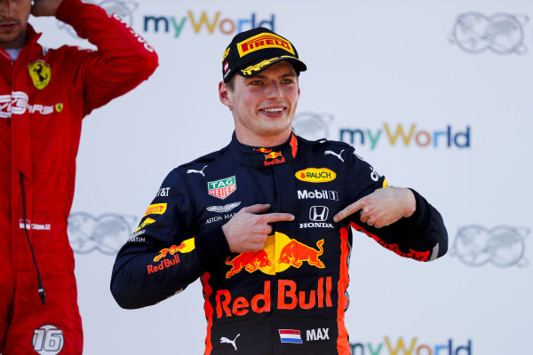Race winner Max Verstappen, Red Bull Racing celebrates on the podium by pointing to the Honda badge on his overalls