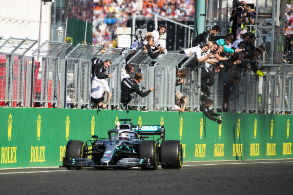 Lewis Hamilton, Mercedes AMG F1 W10, 1st position, is cheered over the finish line by his team