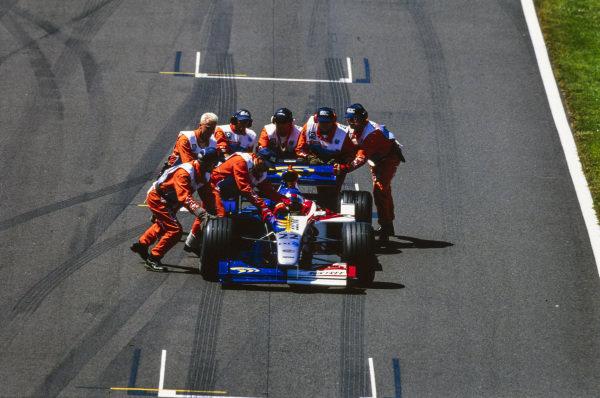 Marshals push the car of Jacques Villeneuve, BAR 01 Supertec, after retirement form the race.