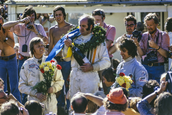 Winner Denny Hulme celebrates victory on the podium with Ronnie Peterson, 2nd position and François Cevert, 3rd position.