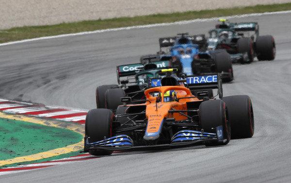 Lando Norris, McLaren MCL35M, leads Lance Stroll, Aston Martin AMR21, Fernando Alonso, Alpine A521, and Sebastian Vettel, Aston Martin AMR21