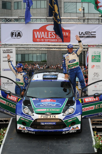 Petter Solberg (NOR) and Chris Patterson (GBR), Ford Fiesta RS WRC celebrate 3rd place on the podium. FIA World Rally Championship, Rd10, Wales Rally GB, Day Three, Cardiff, Wales, 16 September 2012.
