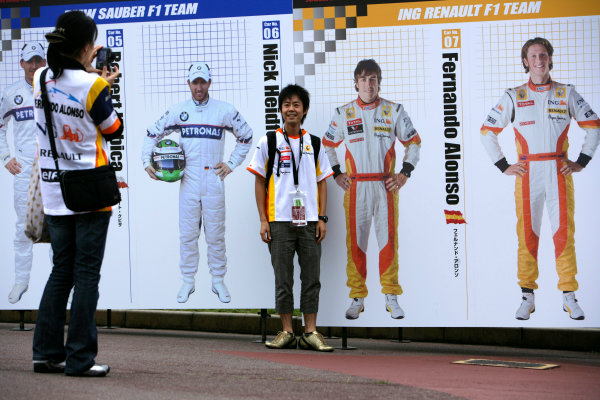 Suzuka Circuit, Suzuka, Japan.1st October 2009.A fan poses for a photo with 2D cut outs of drivers Nick Heidfeld, BMW Sauber F1 09, Fernando Alonso, Renault R29, and Romain Grosjean, Renault R29. Atmosphere. World Copyright: Charles Coates/LAT Photographicref: Digital Image ZK5Y0026