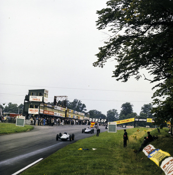 Jim Clark, Lotus 25 Climax, leads Graham Hill, BRM P578, past a slippery surface flag.
