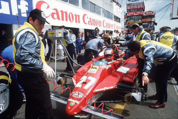 Mechanics work on Gilles Villeneuve's Ferrari 126C2 as he sits in the car.