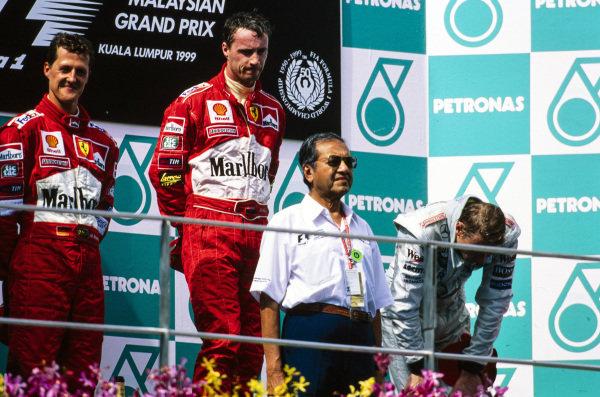 Michael Schumacher, 2nd position, Eddie Irvine, 1st position, and Mika Häkkinen, 3rd position, on the podium.