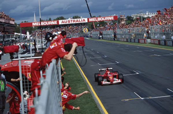 Michael Schumacher, Ferrari F2001, raises his arm in victory, as the Ferrari mechanics celebrate.