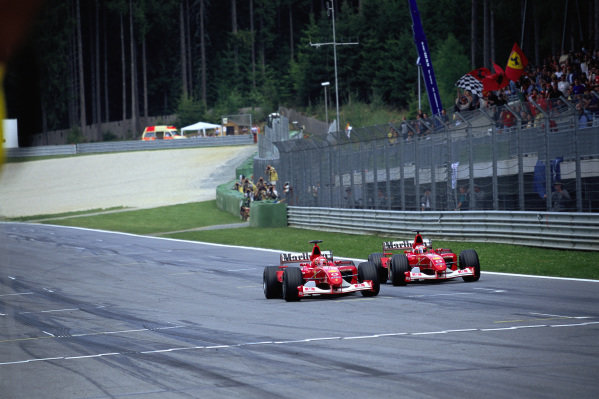 Michael Schumacher, Ferrari F2002, overtaking teammate Rubens Barrichello on the line after the Ferrari team controversially staged the finish.