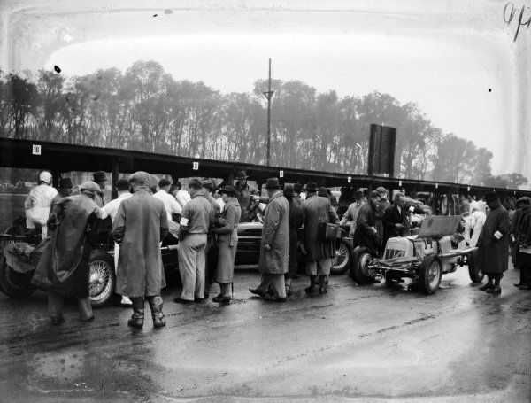 "Fans and race officials look at cars in the pit area. The ERA B driven by ""B. Bira"" can be seen on the right of frame."