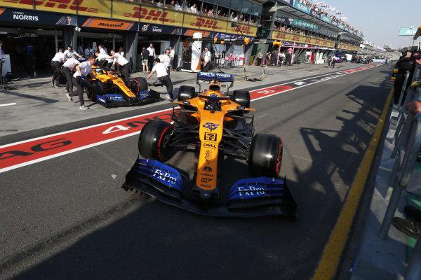 Lando Norris, McLaren MCL34, is returned to the garage as Carlos Sainz Jr., McLaren MCL34, leaves the pits