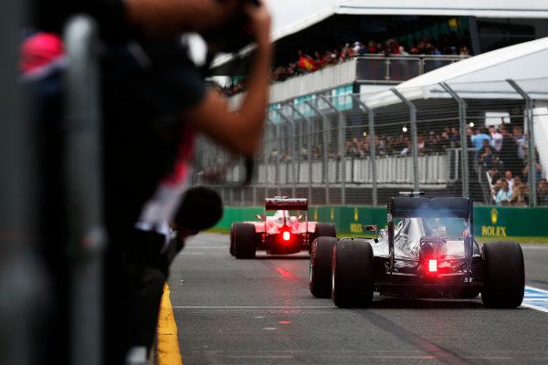 Albert Park, Melbourne, Australia. Saturday 19 March 2016. Kimi Raikkonen, Ferrari SF16-H, leads Lewis Hamilton, Mercedes F1 W07 Hybrid, out of the pit lane. World Copyright: Sam Bloxham/LAT Photographic ref: Digital Image _R6T2592