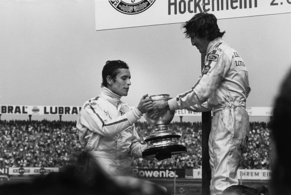 Hockenheim, Germany. 31st July - 2nd August 1970.Jochen Rindt (Lotus 72-Ford), 1st position, offers the winners Ctrophy filled with Champagne to Jacky Ickx (Ferrari 312B), 2nd position, podium, portrait.World Copyright: LAT Photographic.Ref:  3232 - 2A/3.