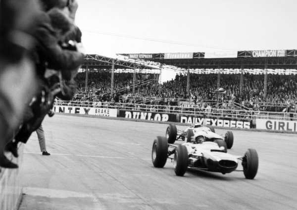 1965 British Grand Prix.Silverstone, Great Britain. 10 July 1965.Bruce McLaren, Cooper T77-Climax, 10th position, and Jim Clark, Lotus 33-Climax, 1st position, action.World Copyright: LAT Photographic