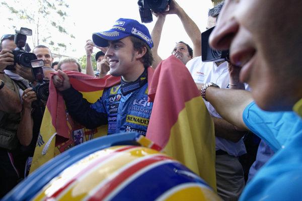 World Champion Fernando Alonso celebrating with a Spanish flag.