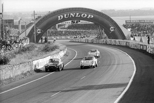 Peter Harper (GBR) / Peter Proctor (GBR) #33 Sunbeam Alpine (Left) retired from the race with a broken head gasket. It is passed by the Porsche 356B 2000GS GT - Porsche 587 of Heinz Schiller (SUI) / Ben Pon (NED), who retired from the race with a blown engine. Le Mans 24 Hours, Le Mans, France, 16-17 June 1963.
