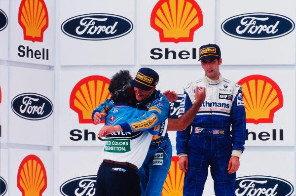 Interlagos, Sao Paulo, Brazil.25-27 March 1994.Team boss Flavio Briatore hugs Michael Schumacher (Benetton Ford) after his win on the podium. Damon Hill (Williams Renault) 2nd position stands behind.Ref-94 BRA 08.World Copyright - LAT Photographic