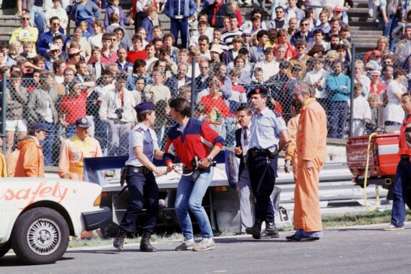 Spa-Francorchamps, Belgium. 1st September 1985. Rd 7.Aphotographer is led away by the police due to the fatal accident to Stefan Bellof, portrait. World Copyright: LAT Photographic.Ref:  85SPA05