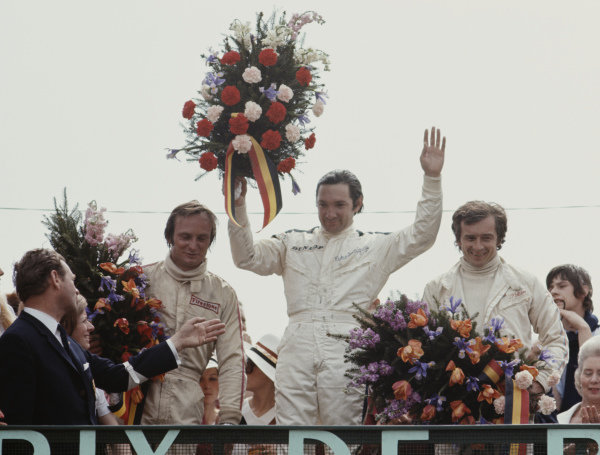 Pedro Rodriguez, 1st position, Chris Amon, 2nd position, and Jean-Pierre Beltoise, 3rd position, celebrate on the podium.