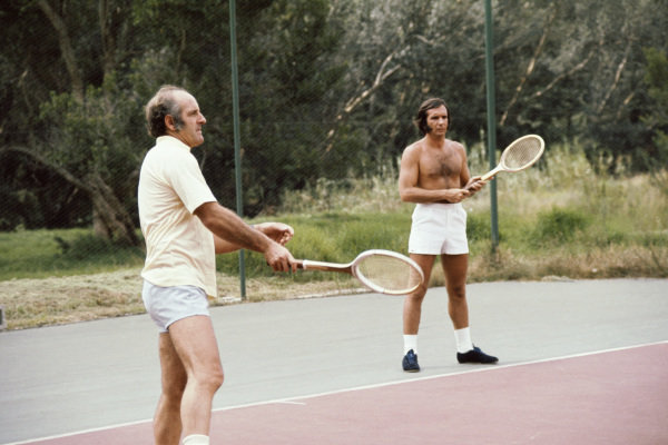 1975 South African Grand Prix. Kyalami, South Africa. 27th February - 1st March 1975. Denny Hulme and Emerson Fittipaldi relaxe by playing tennis, portrait.  World Copyright: LAT Photographic. Ref: 75SA