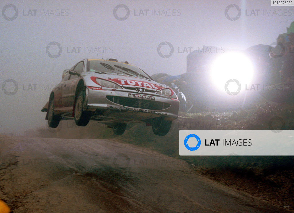 Harri Rovanpera flies over the famous Fafe jump in terrible weather conditions in his Peugeot 206 WRC.