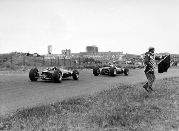 1965 Dutch Grand Prix.Zandvoort, Holland. 18 July 1965.John Surtees, Ferrari 1512, 7th position, leads Jim Clark, Lotus 33-Climax, 1st position, action, flag marshal.World Copyright: LAT PhotographicRef: Autocar b&w print
