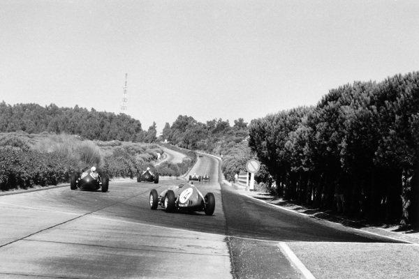 Monsanto, Portugal. 23 August 1959.Tony Brooks, #14 Ferrari Dino 246, 9th position, and Roy Salvadori, Aston Martin DBR4/250, 6th position, chase Ron Flockhart, BRM P25, 7th position, onto the Auto Estrada during the race, action.World Copyright: LAT PhotographicRef: Autosport b&w print. Published: Autosport, 28/8/1959 p274