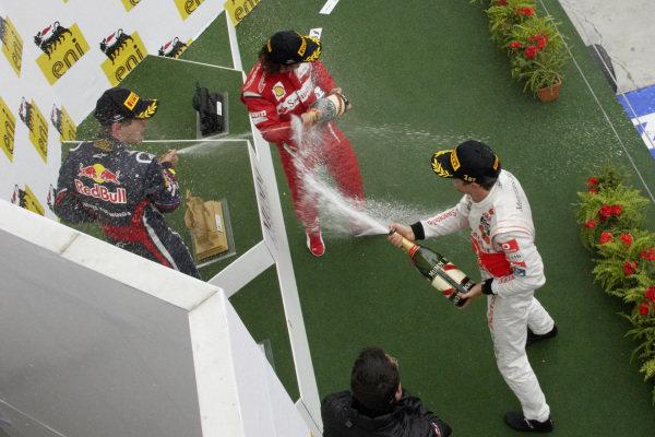 Jenson Button, 1st position, Sebastian Vettel, 2nd position, and Fernando Alonso, 3rd position, celebrate on the podium.