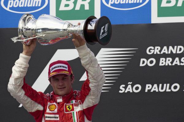 Race winner Kimi Räikkönen shows off his trophy on the podium.