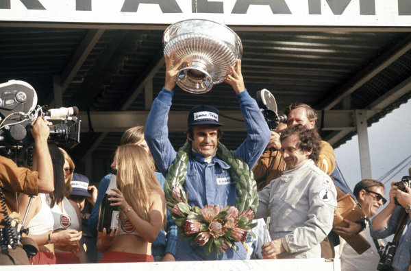 Carlos Reutemann celebrates victory on the podium with Jean-Pierre Beltoise, 2nd position.