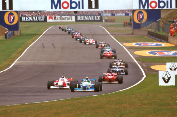 Silverstone, England.12-14 July 1996.Mika Hakkinen (McLaren MP4/11 Mercedes) looks down the inside of Jean Alesi (Benetton B196 Renault) at Stowe with Michael Schumacher heading the rest down along Hangar Straight.Ref-96 GB 10.World Copyright - LAT Photographic