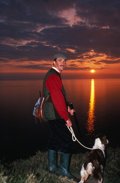 Isle of Man, United Kingdon. 18/4/1989. Nigel Mansell holds a shotgun while walking a dog