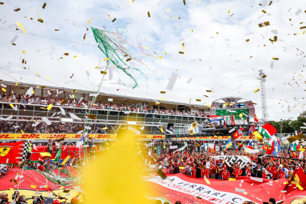 Streamers and confetti fall as the crowd and drivers celebrate at the podium ceremony.