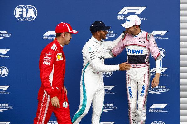 Sebastian Vettel, Ferrari, with Esteban Ocon, Racing Point Force India VJM1, and pole sitter Lewis Hamilton, Mercedes AMG F1.