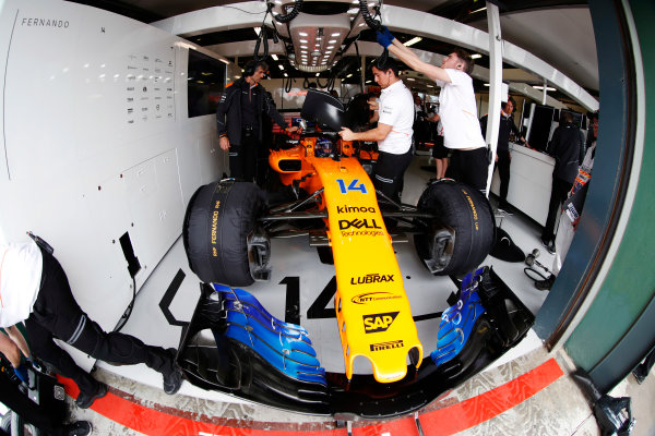 Fernando Alonso, McLaren, in the team's garage, surrounded by mechanics.