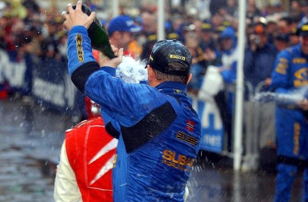(L to R): Rally winner Petter Solberg (NOR) Subaru celebrates by spraying second place finisher Sebastien Loeb (FRA) Citroen with champagne.