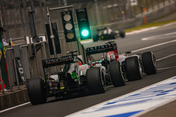 Daniel Ricciardo, Red Bull RB10 Renault, leads Nico Hülkenberg, Force India VJM07 Mercedes, down the pitlane.