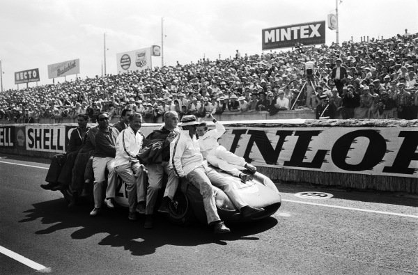 Jochen Rindt rides on the front as the North American Racing Team celebrate victory with their Ferrari 250LM driven by Rindt, Masten Gregory and Ed Hugus. It was the first international race victory for Goodyear tyres and the last, to date, Ferrari outright victory at Le Mans.