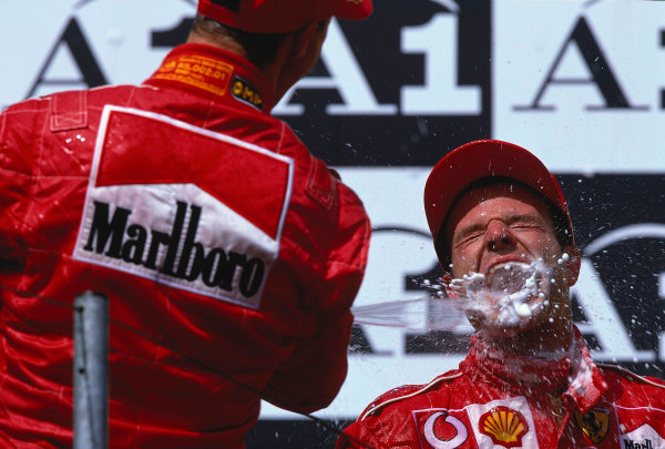 2002 Austrian Grand Prix.A1-Ring, Zeltweg, Austria.10-12 May 2002.Rubens Barrichello (Ferrari) 2nd position is sprayed by team mate Michael Schumacher 1st position on the podium. Rubens stands on the top spot though after he was put there by Michael Schumacher, who was unhappy about the team orders which had ensued in the race.Ref-02 AUT 27.World Copyright - LAT Photographic