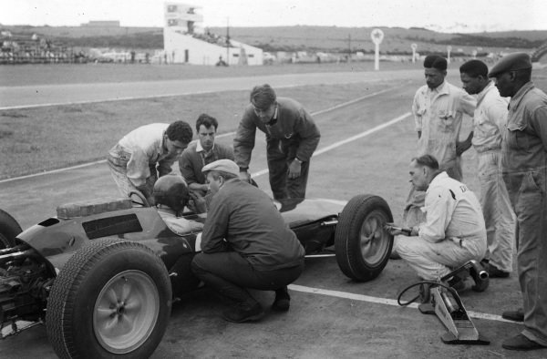 Colin Chapman chats with Jim Clark as he sits aboard Lotus 25 Climax.