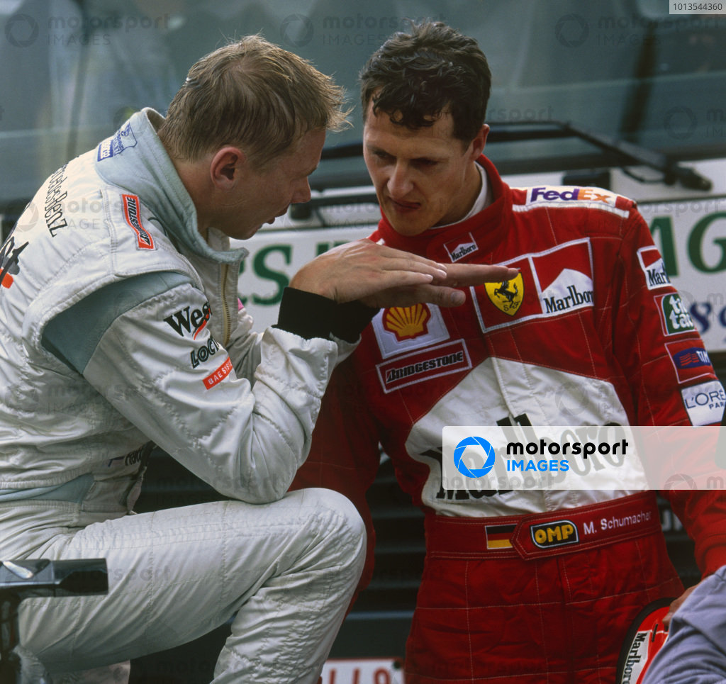 Spa-Francorchamps, Belgium. 25-27 August 2000.  Mika Hakkinen (McLaren MP4/15 Mercedes), 1st position, and Michael Schumacher (Ferrari F1-2000), 2nd position, discuss their battle, which eventually led to Hakkinen passing Schumacher for the lead while lapping Ricardo Zonta on the Kemmel straight.  World Copyright- Steve Tee/LAT Photographic.Ref: Colour Transparency.