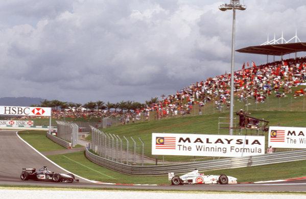 Sepang, Kuala Lumpur, Malaysia.20-22 October 2000.Jacques Villeneuve (B.A R. 002 Honda) followed by Mika Hakkinen (McLaren MP4/15 Mercedes).Ref-35mm A12.World Copyright - Lawrence/LAT Photographic
