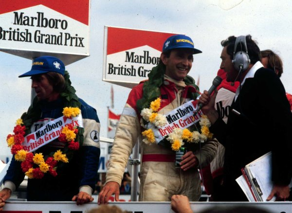 1981 British Grand Prix.Silverstone, England.16-18 July 1981.John Watson (McLaren Ford) is interviewed after winning while Jacques Laffite (Talbot Ligier Matra) stands to his right after finishing 3rd.World Copyright - LAT Photographic
