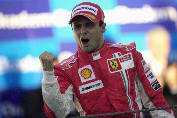 An emotional Felipe Massa celebrates his race victory on the podium.
