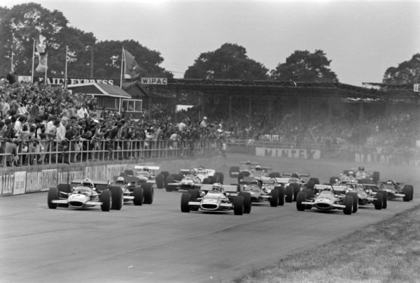 Jochen Rindt, Lotus 49B Ford, leads Jackie Stewart, Matra MS80 Ford, John Surtees, BRM P139, and Denny Hulme, McLaren M7A Ford, head the field at the start of the race.