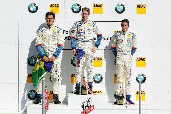 Podium, Sebastian Vettel (GER), ADAC Berlin Brandenburg e.V. (1st, center), Atila de Abreu (BRA), ADAC Mittelrhein e.V. (2nd, left) and Sebastien Buemi (SUI), Lars Kaufmann Motorsport (3rd, right). Formula BMW ADAC Championship 2004, Rd 17&18, Brno, Czech Republic. 18 September 2004. DIGITAL IMAGE